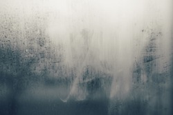 Vintage tone image of rain drop on foggy glass. Blurred grunge abstract overlay texture background with gradient colors.