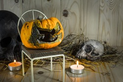 vintage tone image of rotten Halloween pumpkin with candle light and dry grass. Wooden background.