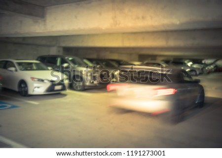 Vintage tone motion blurred entrance to underground parking garage with car entering. Interior of busy concrete basement parking with no vacant lot in suburban Dallas, Texas, USA