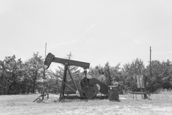 Vintage tone rustic working pump jack pumping crude oil out of well. Pumper, water emulsion at oil drilling site in Gainesville, Texas, US. Old pump jack, oil tanks for Energy, Industrial background
