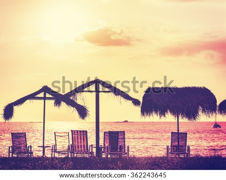 Vintage toned beach chairs and umbrellas at sunset, holidays background.