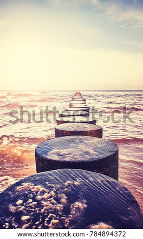 Vintage toned close up picture of an old wooden groyne on a beach at sunset, peaceful natural background, selective focus.