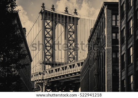 Vintage toned famous view of the Manhattan Bridge and a Brooklyn street sidelined by old brick buildings in New York City #522941218