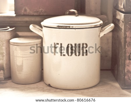 Vintage toned image of an enamel flour tin in an old style kitchen