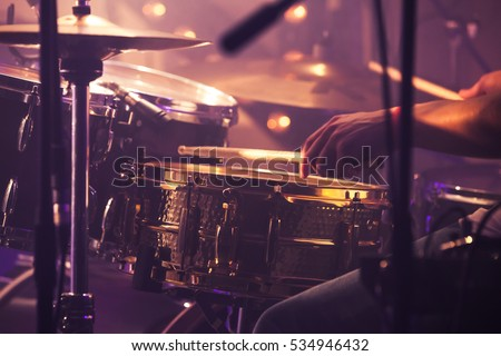 Vintage toned live music background, drummer plays with drumsticks on rock drum set. Closeup photo with soft selective focus