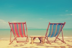 Vintage toned two beach chairs on tropical shore