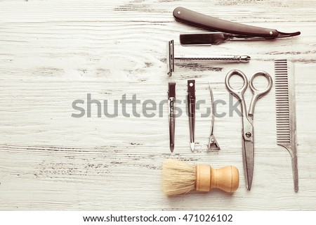 Vintage tools of barber shop on light wooden background