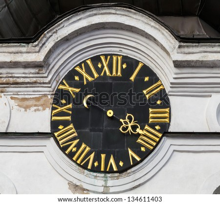 Vintage tower clock with roman numerals on white church wall in old part of Tallinn, Estonia