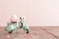 Vintage toy blue mototrcycle with pink heart on wooden table in nursery room