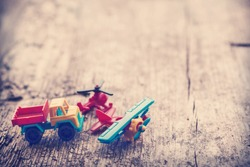 Vintage toy truck, plane with wings and propeller and blue car on wooden table background with copy space