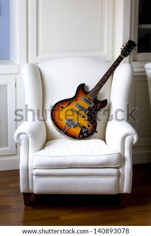 Vintage traditional semi-hollow electric guitar with f-holes on a white  armchair. Electric Guitar on an Armchair.