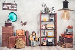 Vintage travel suitcases, backpack, old gramophone, TV, radio, mic, projector, clock, typewriter, quill, books, camera, Teddy Bear, toy plane, signboard, mask. Antiques collectibles. Retro style photo
