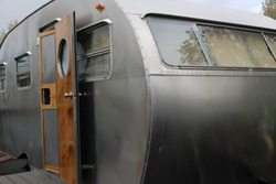 Vintage travel trailer with door open with round window and wood detail.