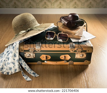 Vintage traveler suitcase with sunglasses, straw hat, old camera and maps.
