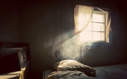 Vintage treated old abandoned bedroom with smoke lit by an open window with curtains