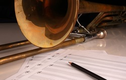 Vintage trombone, pencil and sheet music on a glossy white table and dark background