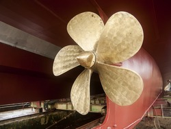 Vintage Tug Brass Propeller Vessel Mounted dry-docked old steam tug boat vessel with solid brass propeller and riveted hull metal plates visible