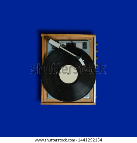 vintage turntable vinyl record player on blue background. retro sound technology to play music #1441252154
