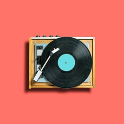 vintage turntable vinyl record player on coral background. retro sound technology to play music. trendy 2019 color concept