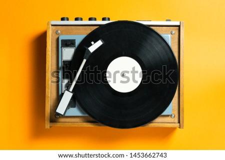vintage turntable vinyl record player on orange background. retro sound technology to play music
