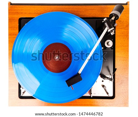 Vintage turntable with a blue vinyl isolated on white. Wooden plinth. Retro audio equipment.
