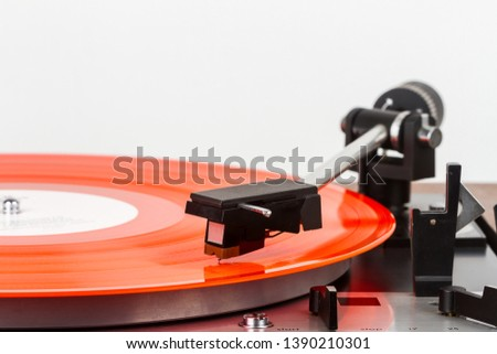 Vintage turntable with a red vinyl isolated on white. Retro audio equipment.
