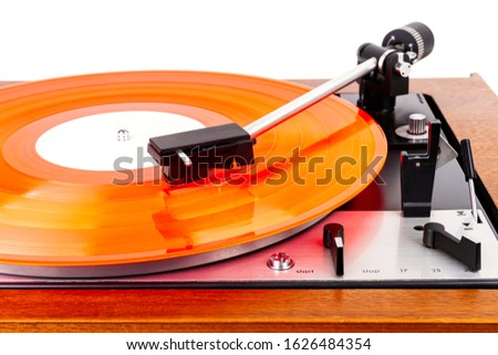Vintage turntable with a red vinyl isolated on white. Wooden plinth. Retro audio equipment.