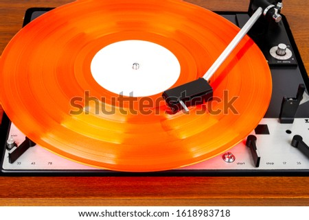 Vintage turntable with a red vinyl. Wooden plinth. Retro audio equipment.