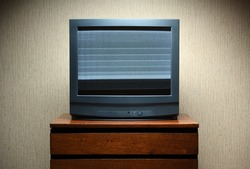 Vintage TV on a wooden antique cabinet, old design in the house. Old black vintage TV with clutter on the screen.