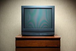 Vintage TV on wooden antique closet, old design in a home.Old black vintage TV.