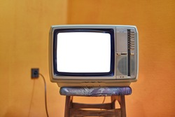 Vintage TV set on a chair with blank white screen