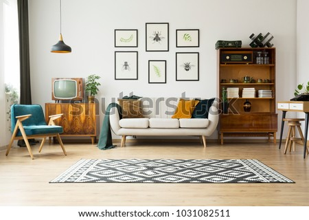 Vintage tv standing on a wooden cabinet next to a comfy couch in a stylish day room interior