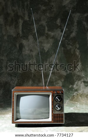 Vintage TV with knobs and antenna over a textured background