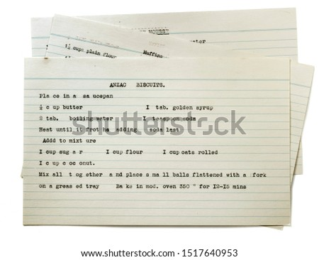 Vintage typed recipe for Anzac biscuits on index card, top view isolated on white. Traditional oatmeal and coconut cookies.