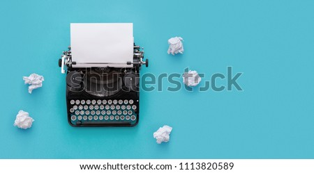 Photo of Vintage typewriter and crumpled papers over blue background with copy space
