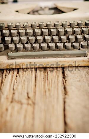 vintage typewriter and flower on the wood desk in vintage color tone
