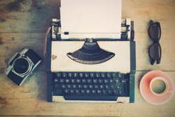 vintage typewriter and vintage camera and coffee on the wood background vintage color tone