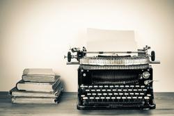 Vintage typewriter, old books on table sepia photo