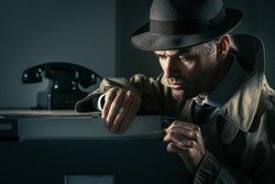 Vintage undercover criminal spy stealing files in a filing cabinet late at night, security and data theft concept