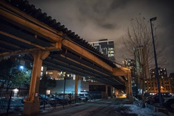 Vintage urban city railway bridge and alley during the winter at night