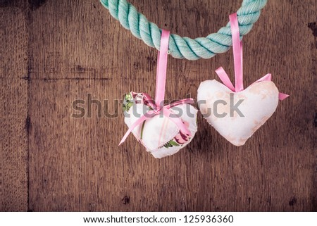 Vintage Valentine wooden background with hearts hanging on rope