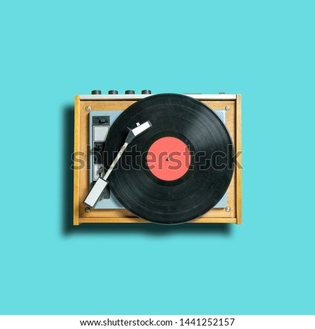 vintage vinyl disc record with coral label on dj turntable on blue background. retro sound technology to play music