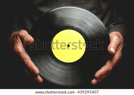 Vintage vinyl record in the hands of an elderly man. #439295407