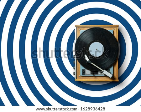 vintage vinyl record player with plate on colorful background with circles pattern in trendy classic blue colors. 2020 modern concept dj turntable
