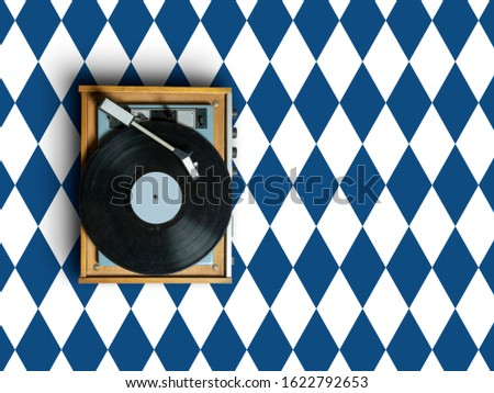 vintage vinyl record player with plate on colorful background with geometric pattern in trendy classic blue colors. 2020 modern concept dj turntable