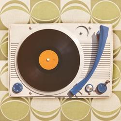 Vintage vinyl turntable player on top of retro green wallpaper