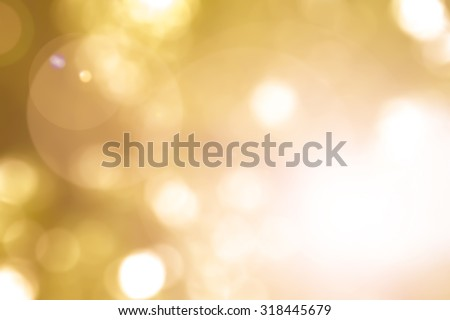 Vintage warm yellow gold color tone blurred nature background of a view looking up through the orange foliage of a tree against the sky facing sun flare and bokeh: Blurred natural greenery bokeh