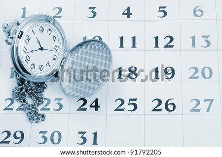 Vintage watch on calendar page close up - stock photo