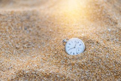 Vintage watch on sand beach with vintage morning warm light, swimming in the time, loosing time, sand watch, outdoor day light