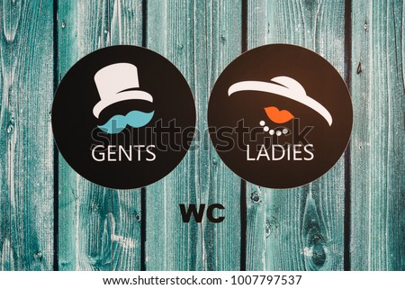 Vintage wc signs for Ladies and Gents on wooden green door. Concept choice